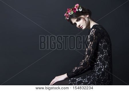 Beautiful black-haired brunette woman with a rim of fresh red and white flowers and green petals on her head in a black lace dress in a sitting pose with head down on black background.
