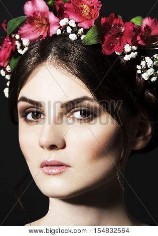 Portrait of beautiful black-haired brunette woman with a rim of fresh red and white flowers and green petals on her head with strong makeup on black background.