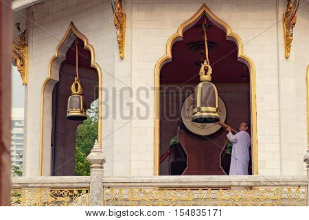 Bangkok, Thailand - January 8, 2016: Woman ringing a bell in Buddhist temple Wat Chana Songkhram. It is located near popular street Khaosan road and district for tourists.