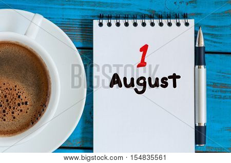 August 1st. Day 1 of month, loose-leaf calendar on blue background with morning coffee cup. Summer time. Unique top view.