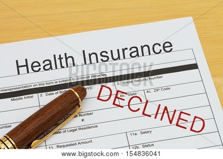 Applying for a Health Insurance Declined Health Insurance application form with a pen on a desk with an declined stamp