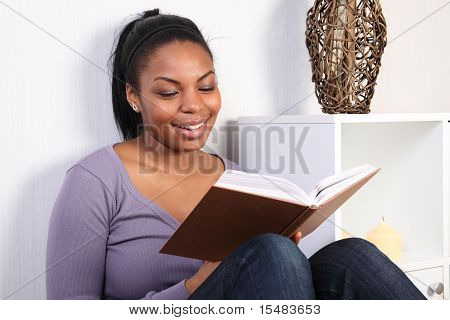 Beautiful Girl Smiling And Enjoying Reading A Book