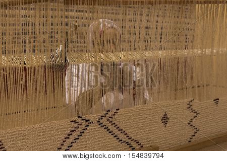 Woman weaving a carpet with traditional techniques on a loom, on a carpet store in the street market of Marrakesh.