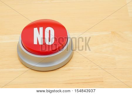 A No red push button A red and silver push button on a wooden desk with text No