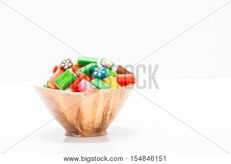 Colorful soft chewy candy in a wooden bowl with ample copy space.