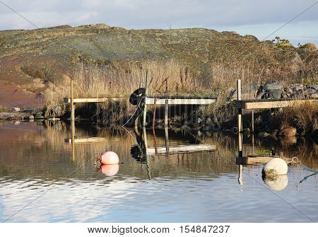 Three small wooden bridges and some buoys in the rural harbor. A cliff en the background