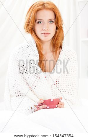 Happy smiling beautiful woman awaking with cup of coffee at bedroom. Girl drinking hot tea on the bed. Attractive young female holding mug with polka dots while sitting in white bedding and pillows.