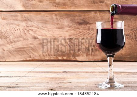 Red Wine. Pouring Red Wine Into Wine Glass On Old Wooden Background