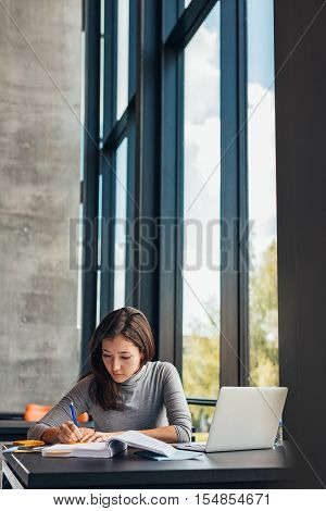 Female student taking notes from books for her study. Young woman sitting at table with books at university library.