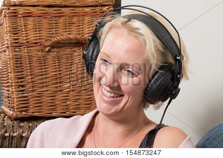 Sitting Blonde Woman In Headphones Tilts Head And Smiles