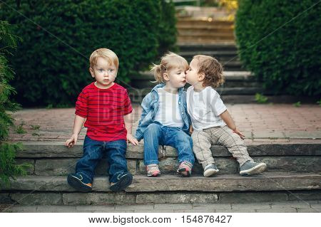 Group of three cute funny adorable white Caucasian children toddlers boys girl sitting together kissing each other love friendship childhood concept best friends forever