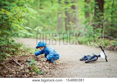 Portrait of cute Caucasian little boy toddler in blue jacket jeans and baseball cap with bike in park playground outside sitting on ground discovering learning new happy childhood lifestyle concept