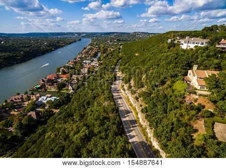 Texas Hill Country Mount Bonnell Road to Texas Texas Hill Country,  Mount Bonnell. Road to Texas aerial Shot over Austin , Texas. Windy road and Houses along the Colorado River or Town Lake with boats driving across the water. The Blue Sky was partly clou