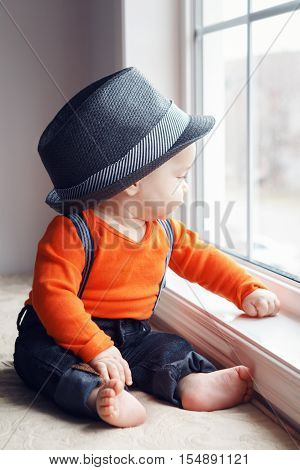 Portrait of cute adorable stylish Caucasian baby boy in hat orange shirt onesie jeans with suspenders barefoot sitting on windowsill looking away natural window light lifestyle