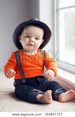 Portrait of cute adorable stylish Caucasian baby boy with black eyes in hat orange shirt onesie jeans with suspenders barefoot sitting on windowsill looking in camera natural window light lifestyle