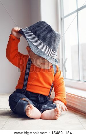 Portrait of cute adorable stylish Caucasian baby boy in orange shirt onesie jeans with suspenders barefoot sitting on windowsill taking off his hat natural window light lifestyle