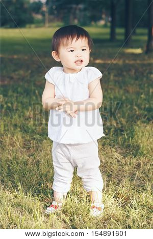 Portrait of cute adorable little Asian girl child baby one year old in white pants shirt standing smiling laughing on field meadow grass on sunset clapping her hands toned with Instagram filters