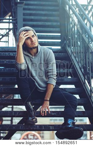 Conceptual art portrait of beautiful handsome pensive young middle east brunette man with blue eyes beard wearing blue hoodie sitting on staircase outside in street looking away