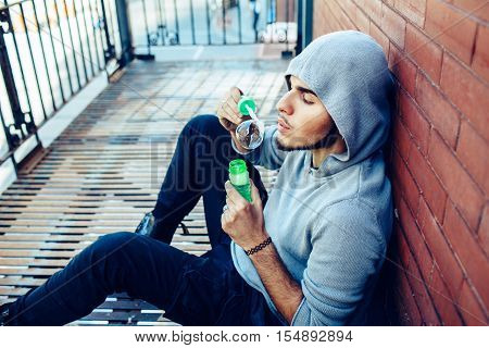 Conceptual art portrait of beautiful young middle east brunette man with beard wearing grey hoodie sitting on staircase outside in city blowing soap bubbles having fun lifestyle