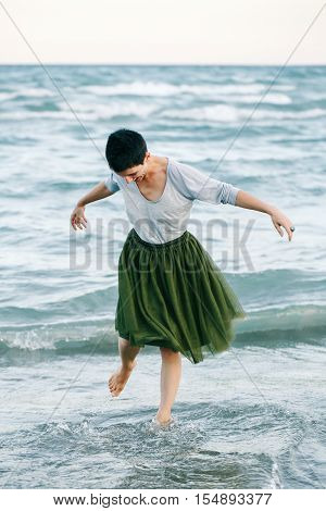 Portrait of beautiful smiling Caucasian white brunette woman with short hair in grey shirt green olive tutu tulle skirt standing barefoot on beach in sea water free happy lifestyle