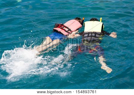Couple man and women snorkeling in blue sea Thailand