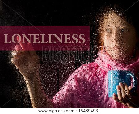 loneliness written on virtual screen. young woman melancholy and sad at the window in the rain, she holding a cup of hot coffee or tea.