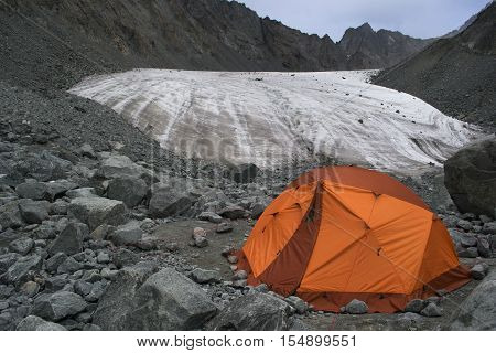 Glacier Moraine with Orange Camping Tent with Cloudy Sky