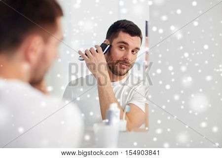 beauty, hygiene, shaving, grooming and people concept - young man looking to mirror and shaving beard with trimmer or electric shaver at home bathroom over snow