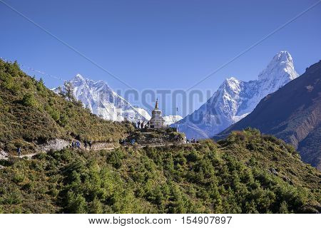 View of a Buddhist stupa with mountain Lhotse and Ama Dablam behind on the way from Namche Bazaar to Tengboche of the everest base camp trekking route.