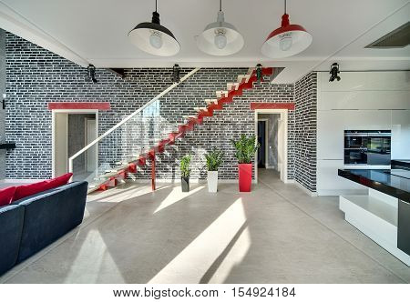 Interior in a modern style with black brick walls and the floor with light tiles. There is a dark sofa with red pillows, a red stair with a glass partition, doors, plants in the pots, kitchen zone.