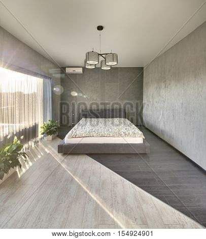 Sunny bedroom in a modern style with concrete walls and a parquet on the floor. There is a bed with a coverlet and pillows, a large window with curtains, plants in the pots, lamps and a conditioner.