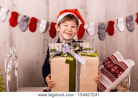 Boy with Christmas gift box with a bow. The boy sits on a bed with a Christmas present