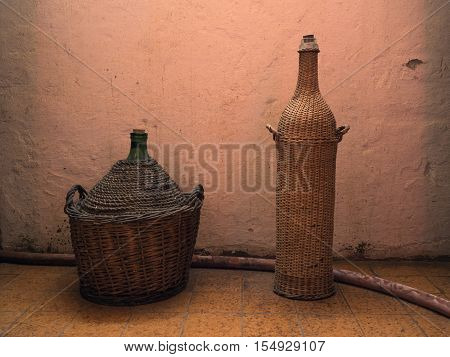 Picture of a two case-bottles of wine against the background of the beige - coloured wall. Background of a two case-bottles of wine in old cellar of the winery.