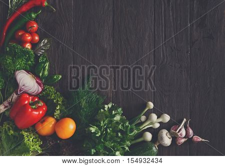 Border of fresh organic vegetables on wood background. Healthy natural food on rustic wooden table with copy space. Garlic, lettuce, carrot, pepper, zucchini and other cooking ingredients top view