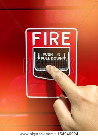a hand reaching and pulling a red fire alarm switch. red fire alarm. Push in pull down.
