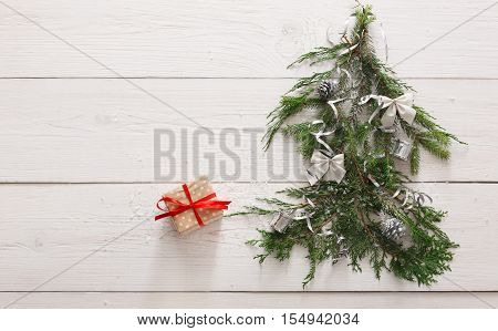 Christmas background. Gift boxes on fir tree branches at white wood. Stylish modern presents in gray paper decorated with red satin ribbon bows. Winter holidays concept, top view, copy space