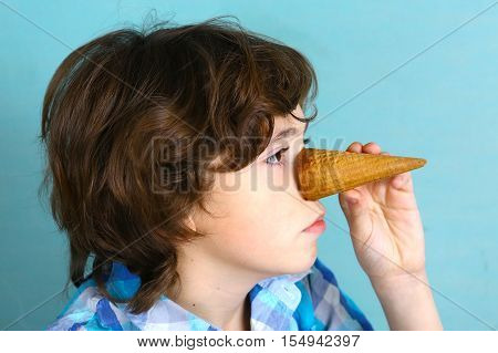 preteen handsome boy grimacing with icecream cone performing pinocchio close up funny photo