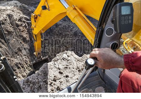 An excavator digging a hole in the ground seen from the cabin.