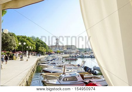 Krk town port Croatian island through curtains. View of the harbour boats docked at marina and the bell tower of the Church of the Assumption of Blessed Virgin Mary with an angel holding a trumpet.