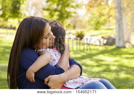 Mixed race Asian mum embracing her young daughter in a park