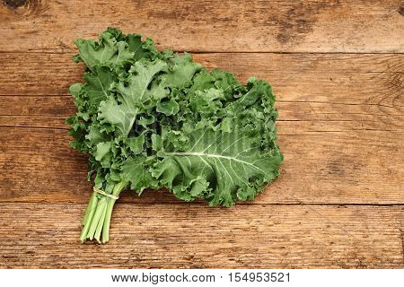 Bunch of broccoli kale on a wooden background.