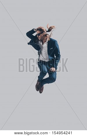Feeling comfortable in his style. Handsome young man in full suit jumping against grey background