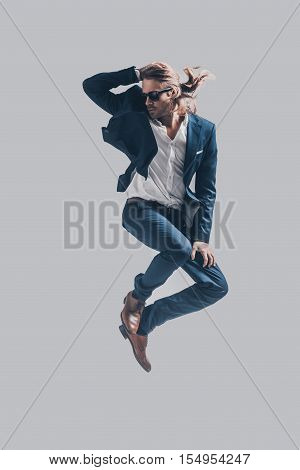 Man in mid-air. Handsome young man in full suit jumping against grey background