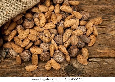 Walnuts and almonds in a burlap bag on a wooden background.