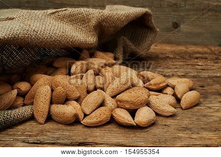 Almond nuts in a burlap bag on a wooden background.
