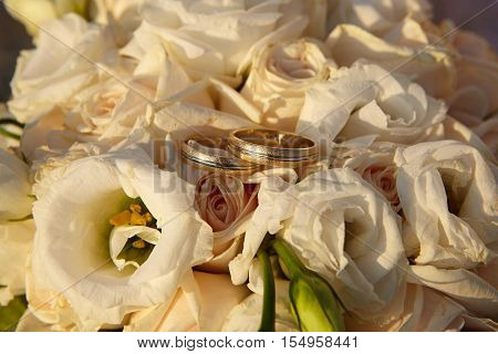 Wedding rings standing on a bunch of flowers.