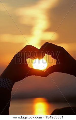 Heart shape silhouette on a beautiful sunset.