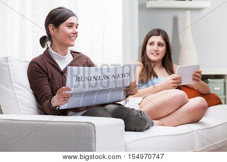 Mother And Daughter Relaxing Reading Together