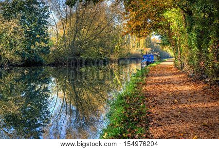 British autumn landscape. Blue narrow boat on colourful canal