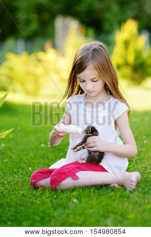 Llittle Girl Feeding Small Kitten With Milk